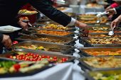 stock photo of buffet lunch  - people group catering buffet food indoor in luxury restaurant with meat colorful fruits  and vegetables - JPG