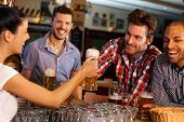 picture of bartender  - Happy friends drinking beer at counter in pub - JPG