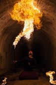 stock photo of fire-breathing  - Fire artist blowing fire from his mouth - JPG