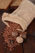 Cloth bag with buckwheat groats and spices on wooden background