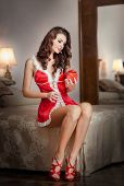 Young Santa holding a gift, boudoir shoot. Attractive brunette with long hair wearing lingerie