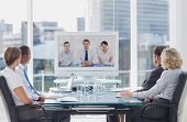 stock photo of coworkers  - Business team having video conference with another business team in office - JPG