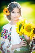 Young girl wearing Romanian traditional blouse holding sunflowers outdoor shot. Beautiful girl