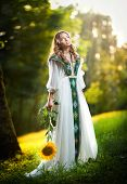 pic of sunflower  - Young woman wearing a long white dress holding a sunflower outdoor shot - JPG