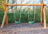 stock photo of tire swing  - Double swing of wood at public school playground - JPG