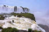 The grand Iguazu Falls on the Brazilian side. Multi-tiered cascades of water roar of lush jungle. Ov