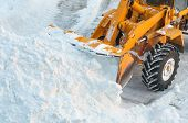 image of bulldozer  - Excavator is clearing the streets after snow drifts - JPG