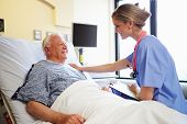 image of geriatric  - Nurse Talking To Senior Male Patient In Hospital Room - JPG