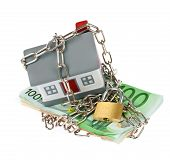 stock photo of plastic money  - House model toy plastic with bills chain and padlock - JPG
