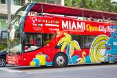 MIAMI,US - NOVEMBER 24,2013:Open deck sightseeing bus at Miami Beach. International tourists make up