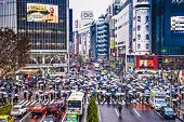 TOKYO, JAPAN - DECEMBER 15, 2012: Pedestrians sheild themselves from rain with umbrellas at Shibuya