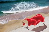 woman with a red tissue on the beach