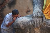 senior man watching old buddha statue past magnifier glass lens