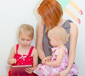 Mother And Her Daughters Using Tablet Pc.