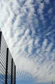 The Sky With Clouds And A Fence