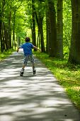 foto of inline skating  - boy on inline skates rolling through the park