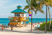MIAMI,USA - MAY 26,2014 : People enjoying the beach near an iconic lifeguard tower in South Beach on a beautiful summer day