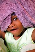 pic of child missing  - Child with towel over head with one eyes showing and smiling to show two missing teeth.