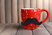 Cup with mustache on table on wooden background