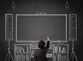 Young businessman standing and enjoying home cinema system sketched on a chalkboard