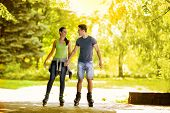 Young couple holding hands and roller-skating in the park