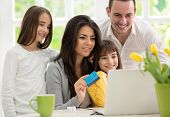 Family shopping online, two twins girls  wit father and mother enjoying in shopping