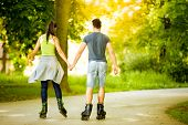 couple ride rollerblades in the park, back view