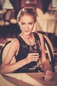 Beautiful young girl with glass of red wine alone in a restaurant