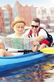 A picture of a young couple with a map in a canoe