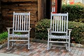 Two gray Adirondack chairs on brick