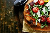 Italian pizza with rucola and cherry-tomatoes
