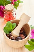 Essential Oil In Glass Bottle, Dried Rose-hip Berries And Rose Hip Flowers