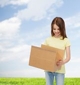 advertising, childhood, delivery, mail and people - smiling girl holding open cardboard box and looking into it over natural background