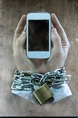 image of addict  - Hands of caucasian businessman addicted to mobile phone bond and locked with iron chain wrists in smartphone internet addiction and slave to online network addict concept - JPG