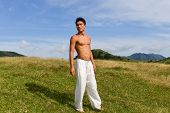 Image of handsome man walking over mountain grass