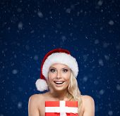 Pretty woman in Christmas cap hands present wrapped with red paper, on blue background
