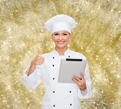 cooking, holidays, technology and people concept - smiling female chef, cook or baker with tablet pc computer showing thumbs up over yellow lights background
