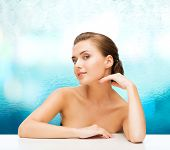 beauty, health and people concept - smiling beautiful woman with clean perfect skin over blue glass background