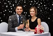 celebration, christmas, holidays and people concept - smiling couple clinking glasses of sparkling wine at restaurant over black snowy background