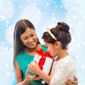 christmas, holidays, family and people concept - happy mother and child girl with gift box over blue lights background