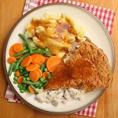 Chicken pie served with mashed potato, vegetables and gravy.