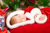foto of christmas baby  - Baby in Santa costume sleeping at the Christmas tree with gifts - JPG