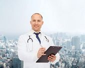 medicine, profession, urban life and healthcare concept - smiling male doctor with clipboard and stethoscope writing prescription over city background