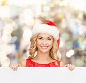christmas, x-mas, people, advertisement and sale concept - happy woman in santa helper hat with blank white board over lights background