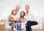 family, people, accommodation and happiness concept - smiling parents and two little girls moving into new home over snowflakes background