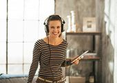 Portrait Of Smiling Young Woman Listening Music In Headphones In