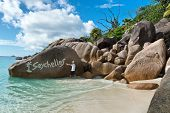 Man standing in the shallow surf pointing to a painted Seychelles sign on a giant granite boulder on the beach at Anse Lazio, Praslin, Seychelles