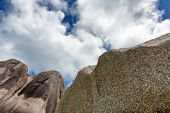 Worms Eye View of Huge Historic Rocks at Seychelles with White and Blue Sky Background.