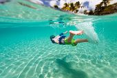 Cute teenage boy swimming underwater in shallow turquoise water at tropical beach