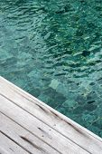 Close Up of Swimming Pool Water and Edge of Wooden Decking